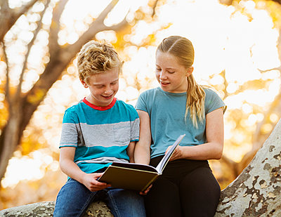 United States, California, Mission Viejo, Boy (10-11) and girl (12-13) sitting on tree branch and reading book - p1427m2271661 by Erik Isakson