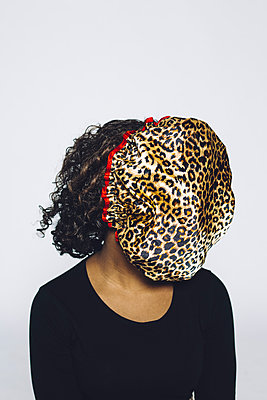 Woman with shower cap in leopard print in front of her face - p1621m2228884 by Anke Doerschlen