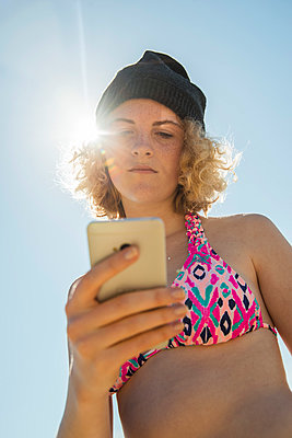 Teenage girl using her smartphone on the beach - p300m965443f by Uwe Umstätter
