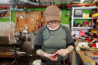 Female plumber working in workshop - p312m2262882 by Phia Bergdahl