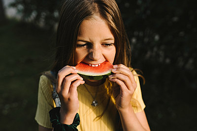 Girl eating watermelon on sunny day - p426m2237920 by Maskot