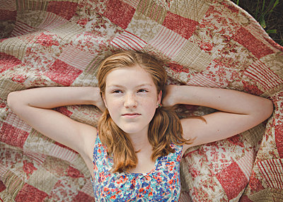 Caucasian girl laying on blanket - p555m1409704 by Shestock