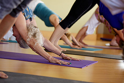 Group of mixed age women practicing yoga - p924m821502f by Natalie Faye
