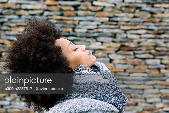 Young woman with eyes closed in warm clothing by stone wall - p300m2257517 by Xavier Lorenzo