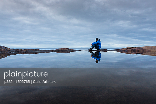 Man sitting by a rock pool in Vasterbotten, Sweden - p352m1523765 by Calle Artmark