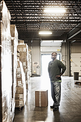 African American male warehouse worker checking inventory on stacks of cardboard boxes holding products in a large distribution warehouse with loading dock door in the background. - p1100m1575478 by Mint Images