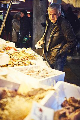 Mann mit Geldschein auf einem Fischmarkt mit Krustentieren - p1312m2082186 von Axel Killian