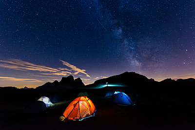 Italy, Dolomites, Milky Way over Monte Pelmo with tents of camp in the foreground - p300m1189125 by Lorenzo Mattei