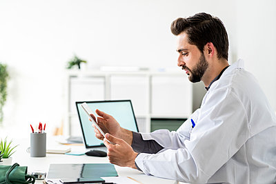 Male healthcare worker using digital tablet while sitting at desk - p300m2275471 by Giorgio Fochesato