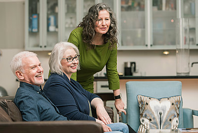 Happy seniors relaxing at home - p429m1206946 by Colin Hawkins