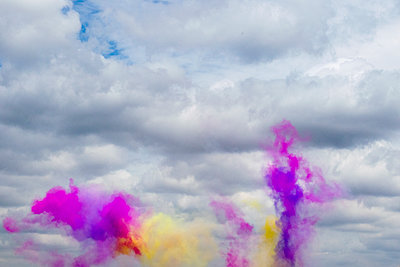 Bright yellow and purple smoke columns against a cloudy sky - p967m2072991 by Wessel Wessels