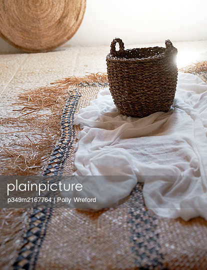 Basket and linen with woven floor mat in Sicilian home - p349m2167764 by Polly Wreford