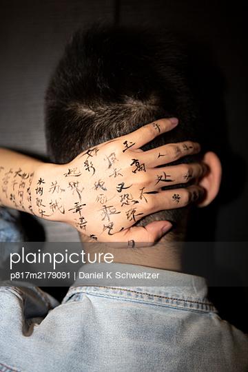 Tattooed hand touches neck of Asian man - p817m2179091 by Daniel K Schweitzer
