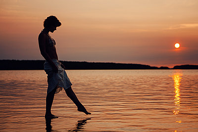 Russia, Silhouette of a woman at sunset on Lake Onega - p1642m2245287 by V-fokuse