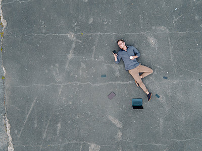 Young businessman with coffee to go lying on tarmac using mini tablet, quadcopter view - p300m1535948 by Kniel Synnatzschke