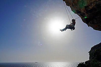 Rock climber lowering off after ascending a steep climb on the cliffs of Malta, Mediterranean, Europe - p871m2003550 by David Pickford