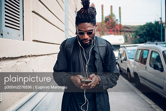 Young man with in-ear headphones using mobile phone on footpath - p300m2276536 by Eugenio Marongiu