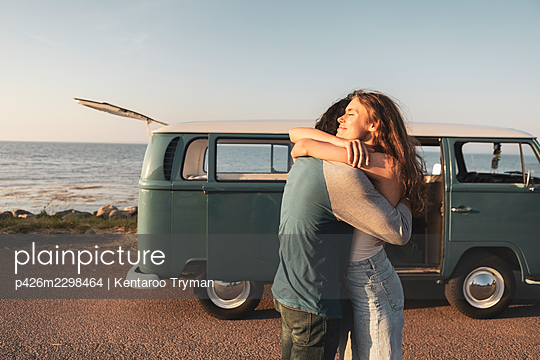 Young couple embracing by sea on road - p426m2298464 by Kentaroo Tryman