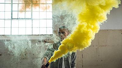 Young man holding a smoke maker producing yellow smoke - p1315m2130279 by Wavebreak