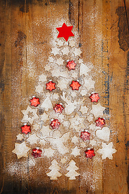 Christmas cookies and red star-shaped Christmas baubles forming Christmas Tree on wooden background - p300m2012561 by Gaby Wojciech