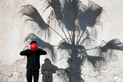 Morocco, Essaouira, man wearing a bowler hat holding red balloon in front of his face at a wall - p300m2104348 by Petra Stockhausen