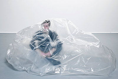 Man with plastic sheet covering - p4020307 by Ramesh Amruth
