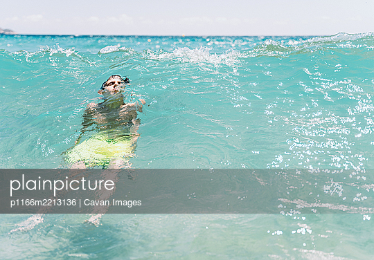 relaxed white boy with closed eyes diving a wave in the sea in summer - p1166m2213136 by Cavan Images