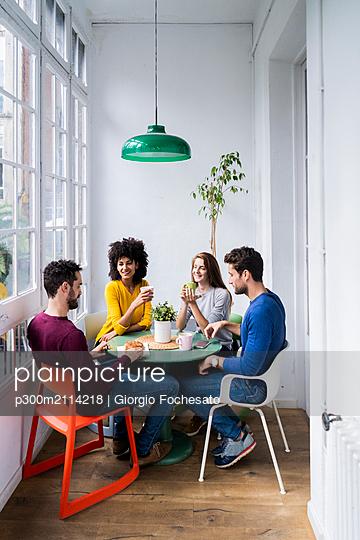 Four friends at home having coffee break - p300m2114218 von Giorgio Fochesato