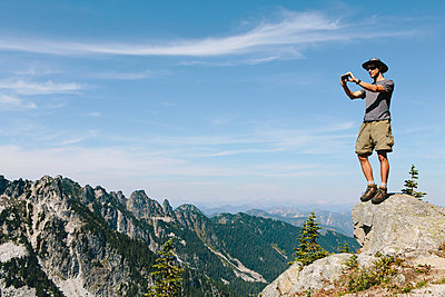 A hiker on a mountain summit, holding a smart phone, at the top of Surprise Mountain, in the Alpine Lakes Wilderness, in Mount Baker-Snoqualmie National Forest.  - p1100m875956f by Paul Edmondson