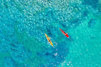 Drone shot of couple kayaking in sea - p1166m2040171 by Cavan Images