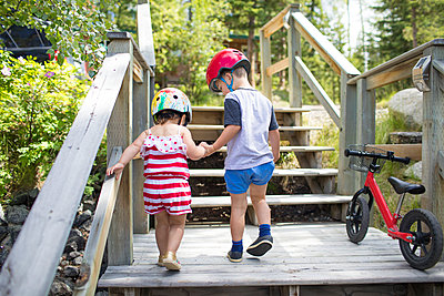 Brother holding hands with sister helping her up wooden staircase. - p1166m2147321 by Cavan Images