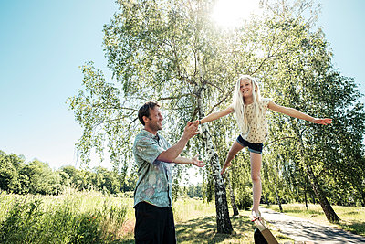 Father helping daughter balancing on a bench in park - p300m2160740 by Wilfried Feder