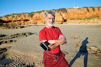 Mature man with arms crossed standing at beach during sunny day - p300m2275761 by Kiko Jimenez