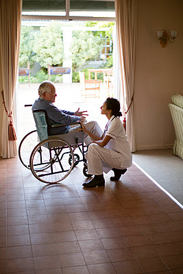 Nurse talking to patient in wheelchair - p555m1305749 by Resolution Productions