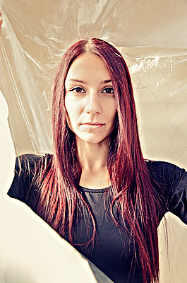 Portrait of young woman standing under plastic sheet - p577m2038713 by Mihaela Ninic