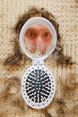 Scattered hair-ends and hand mirror - p676m1525955 by Rupert Warren