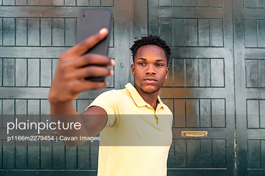 young african man making a selfie - p1166m2279454 by Cavan Images