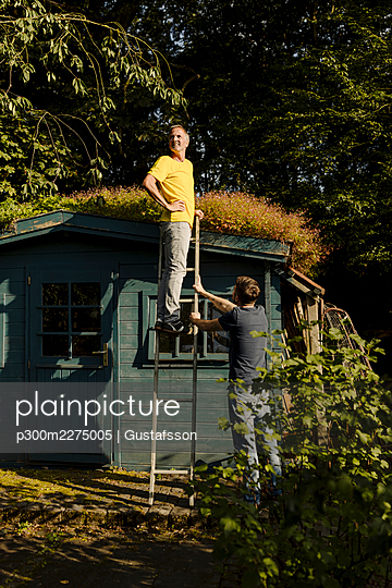 Thoughtful man standing on ladder supported by son in back yard - p300m2275005 by Gustafsson