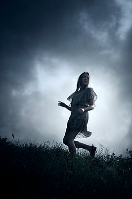 Woman Running on Grass Against Gloomy Sky - p1248m1589941 by miguel sobreira