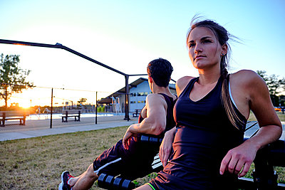 Athletes sitting on bench in public park with sunset behind, Montreal, Quebec, Canada - p1362m2024398 by Charles Knox
