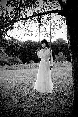Woman in white dress standing on swing - p1521m2215047 by Charlotte Zobel