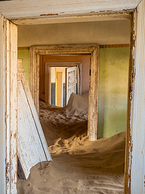Africa, Namibia, inside a house of ghost town Kolmanskop, wooden doors and sand - p300m1579373 by Roy Jankowski