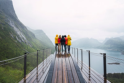 Norway, Senja island, rear view of friends standing on an observation deck at the coast - p300m2042283 by Kike Arnaiz