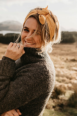 UK, Scotland, Loch Lomond and the Trossachs National Park, portrait of smiling young woman in rural landscape - p300m2104023 by letizia haessig photography