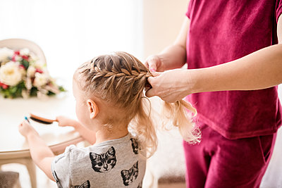 Woman braiding girl's hair at home - p300m2198197 by Ekaterina Yakunina