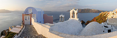 View of Oia village in warm morning light with cobbled path at Santorini - p300m718965f by Martin Rügner