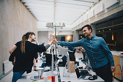 Male and female computer programmers giving high-five over desk in office - p426m1493888 by Maskot