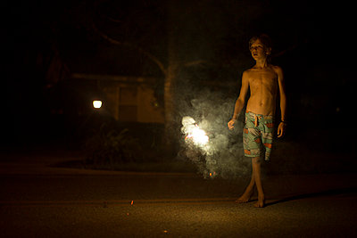 Portrait of boy at night with fireworks in background Destin; Florida; USA - p429m859908 by Raphye Alexius