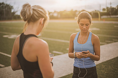Athletes listening to mp3 players on sports field - p555m1411104 by John Fedele