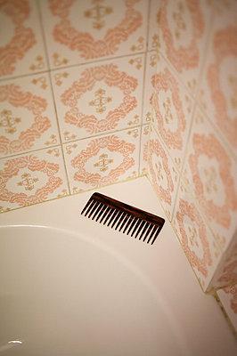 Comb lying in the corner of a bathtub - p5861313 by Kniel Synnatzschke